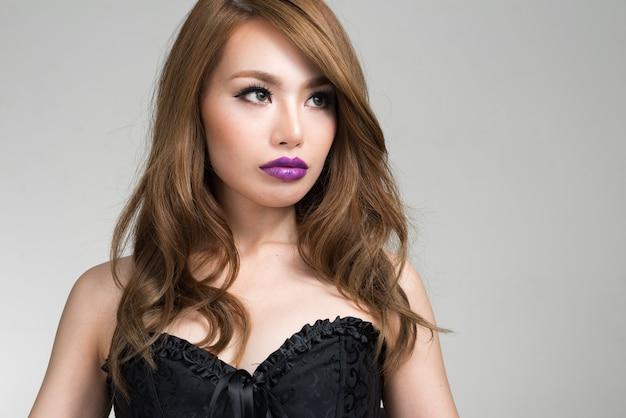 Giovane bella donna giapponese che indossa corsetto come concetto sexy contro il muro bianco