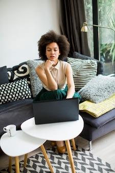 La giovane e bella signora con i capelli ricci lavora sul quaderno mentre si siede sul divano di casa