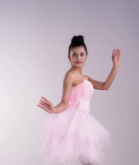 Giovane bella laica che indossa un completo rosa, alza le mani in aria