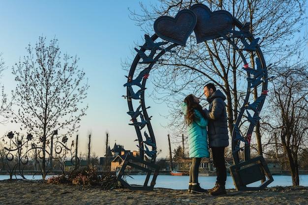 Giovani belle coppie amorose che camminano nel parco cittadino vicino al lago il giorno di san valentino.
