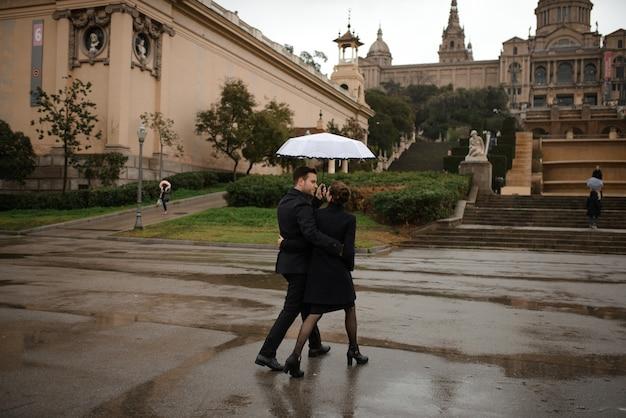 La giovane bella coppia ispanica amorosa cammina sotto un ombrello durante la pioggia in plaza spagna. coppia in posa sullo sfondo del museo nazionale d'arte della catalogna.