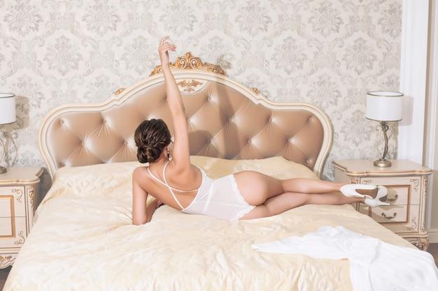 Giovane bella ragazza felice di lusso in biancheria bianca in camera da letto in interni di design sul letto