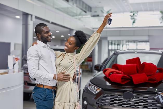Giovane e bella coppia sposata in showroom di automobili