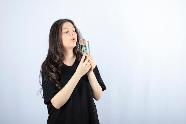 Giovane bella modella che elimina la polvere di trucco con i pennelli sul muro bianco.