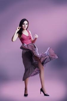 Giovane bellissima modella in posa in luce rosa su sfondo grigio in studio in top e gonna
