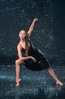 La giovane bella ballerina moderna che balla sotto le gocce d'acqua in studio blu aqua