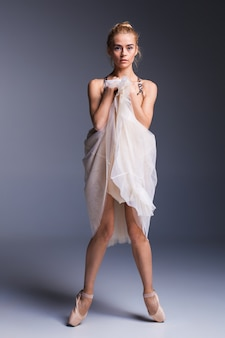 Giovane bella ballerina in stile moderno in posa su uno sfondo di studio