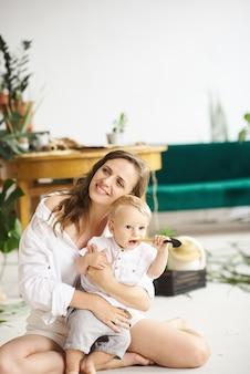 Una giovane e bella mamma gioca con il suo bambino sul pavimento accanto a piante e divano verde