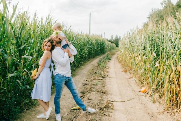 Giovane bella mamma, forte papà caucasico che gioca con il loro grazioso piccolo figlio biondo in un campo di grano.