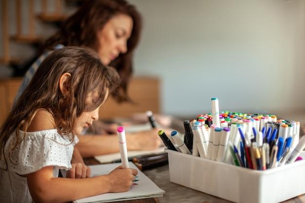 La giovane bella madre e la figlia carina disegnano un motivo a mandala insieme a pennarelli artistici e colorano...