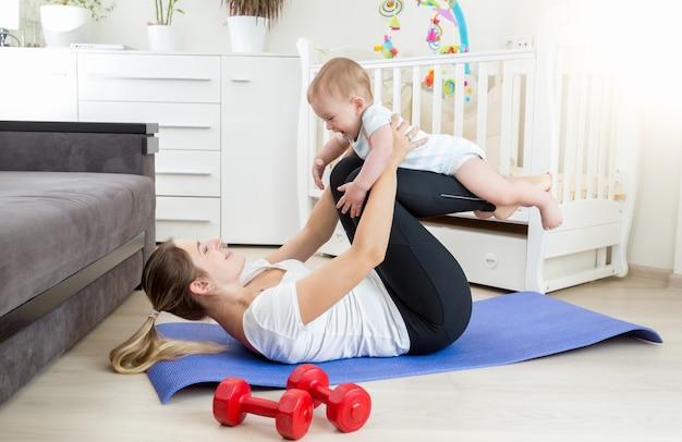 Giovane bella madre che fa esercizio di yoga con il suo bambino sul pavimento in soggiorno