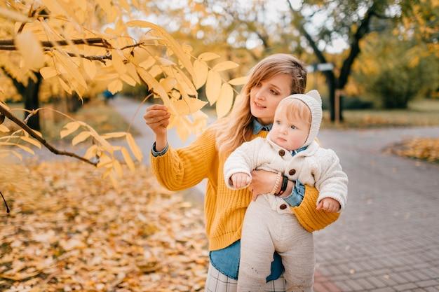 La giovane bella madre gode di trascorrere del tempo nel parco in autunno con il suo bambino piccolo.