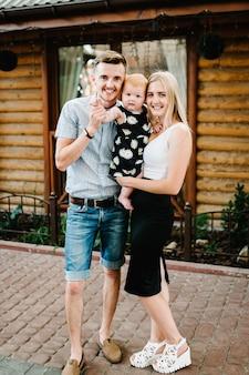 Giovane bella madre e padre con una bambina sulle sue mani in piedi su una casa in legno. bambino. famiglia felice.