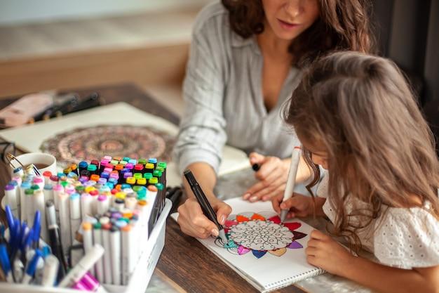 La giovane bella madre aiuta sua figlia a disegnare un grande fiore nello stile del disegno zen circolare ...