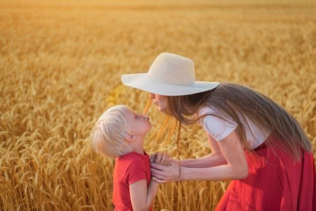 Giovane bella madre e figlio sullo sfondo del campo di grano. rapporto armonioso in famiglia.