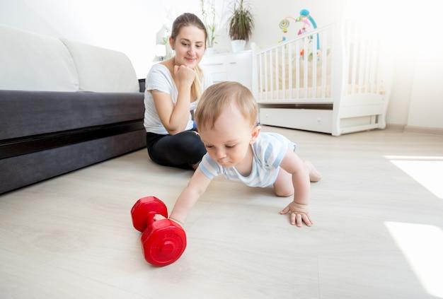 Giovane bella madre con il suo bambino che si esercita con i manubri sul pavimento in soggiorno