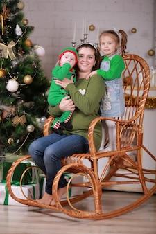 Giovane bella madre con suo figlio bambino in costume da elfo e bambina seduta sulla sedia a dondolo vicino all'albero di natale.