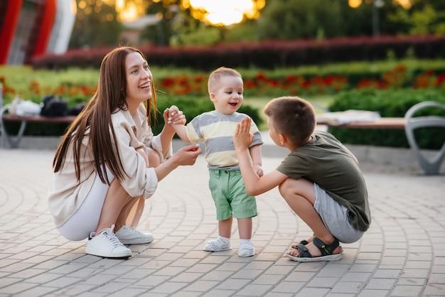 Una giovane bella madre con due ragazzini sta giocando nel parco durante il tramonto. felice passeggiata in famiglia con i bambini nel parco.