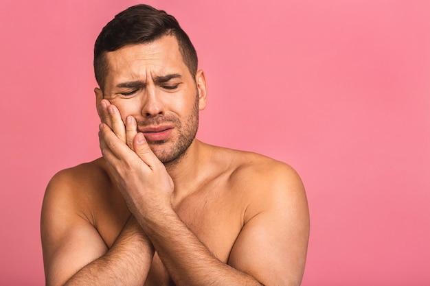 Giovane bello uomo nudo in un bagno che soffre di mal di denti