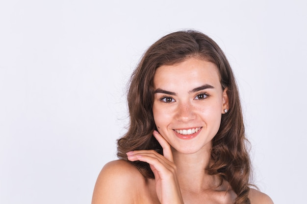 Giovane bella donna dalla pelle morbida e pulita naturale con lentiggini trucco leggero sul muro bianco con spalle nude