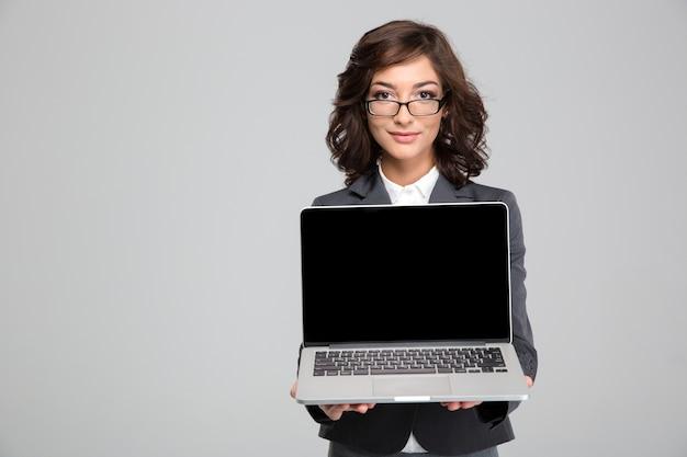 La giovane bella impiegata con gli occhiali tiene in mano un computer portatile di fronte a sé