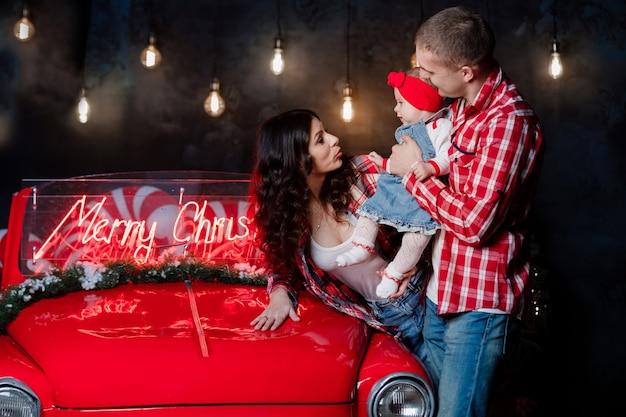 Giovani bei genitori che tengono la loro piccola figlia carina tra le braccia divertendosi vicino all'auto retrò in studio. aspetto familiare di natale. scenario di capodanno.