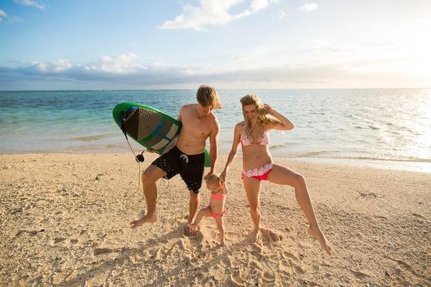 Genitori giovani e belli che giocano con sua figlia sulla spiaggia