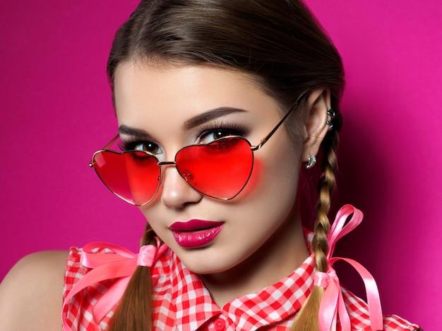 La giovane bella donna allegra guarda sopra i suoi vetri rossi a forma di cuore. san valentino, amore o concetto di festa a tema. occhi smokey e trucco labbra rosse.