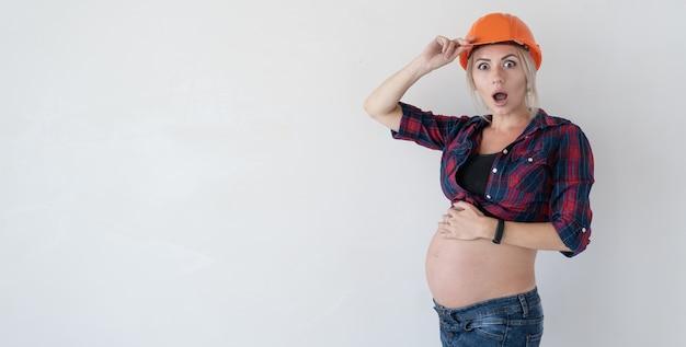 Giovane bella donna bionda incinta. vestiti per la ristrutturazione della casa. camicia a quadri rossi e visiera. l'emozione della sorpresa e dello shock. una mano rimuove il copricapo. copia spazio