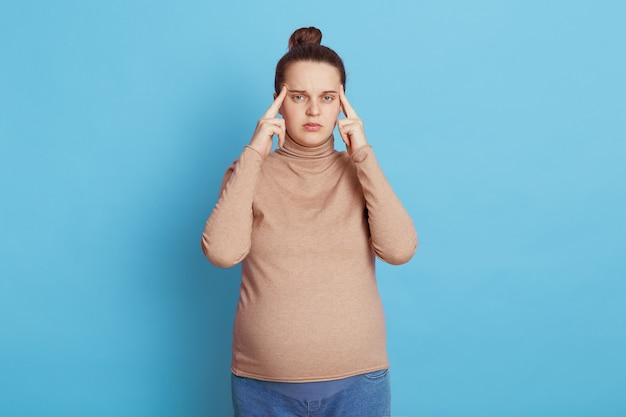 Giovane bella ragazza incinta che prevede bambino, in posa con pensieroso isolato sull'azzurro