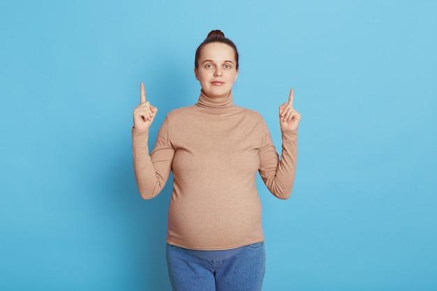Giovane bella ragazza incinta con il panino dei capelli che prevede la posa del bambino isolata sull'azzurro