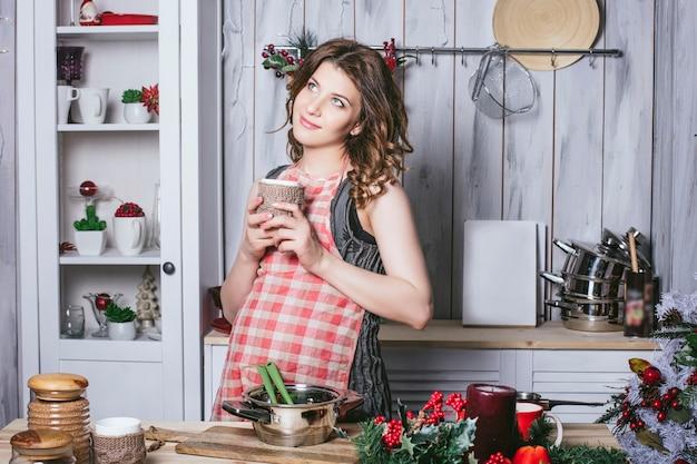 Giovane bella incinta con a casa in cucina sorridendo felice