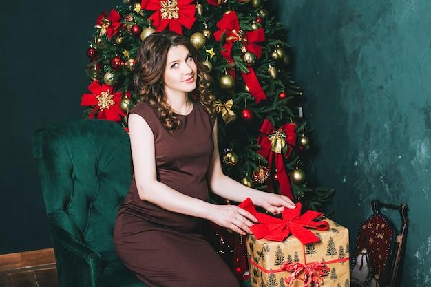 Giovane bella donna incinta a natale con un bellissimo albero di natale decorato con