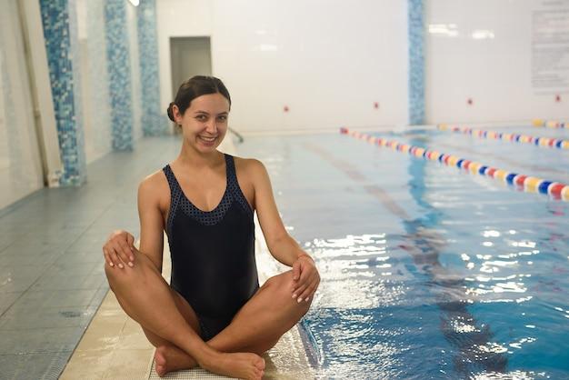 Giovane bella donna incinta vicino alla piscina.