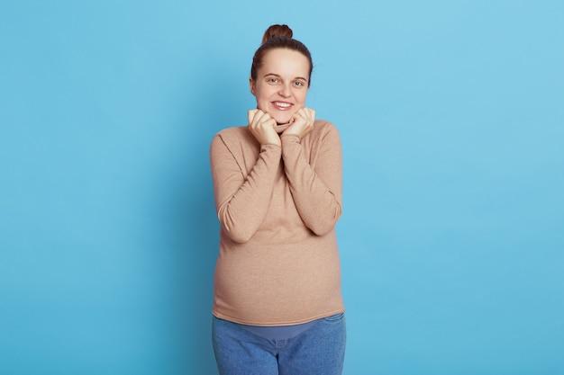 Condizione della giovane bella donna incinta isolata sull'azzurro
