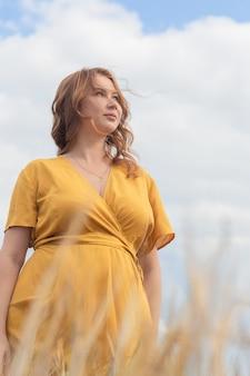 Una giovane bella donna incinta in un vestito giallo e un cappello cammina attraverso un campo di grano arancione in una soleggiata giornata estiva