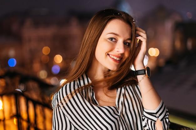 Giovane bella donna graziosa che sorride e che posa alla via della città nella notte contro il fondo del bokeh delle luci della sera.