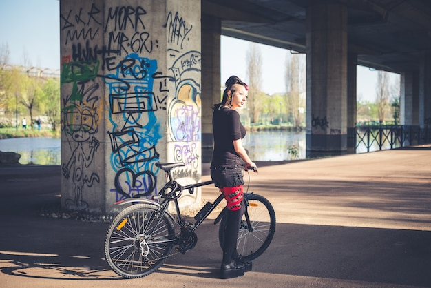 Bici di guida della giovane ragazza bella punk scura