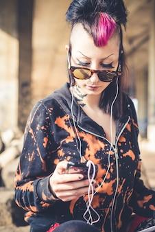 Giovane bella ragazza punk scuro utilizzando tablet