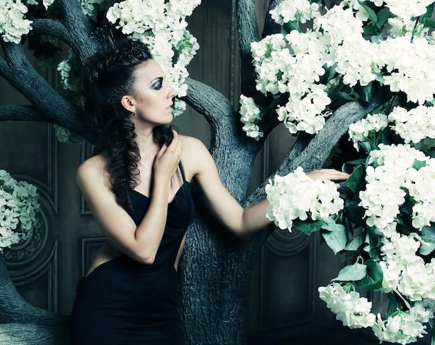 Giovane bella regina in abito nero in posa vicino all'albero con grandi fiori