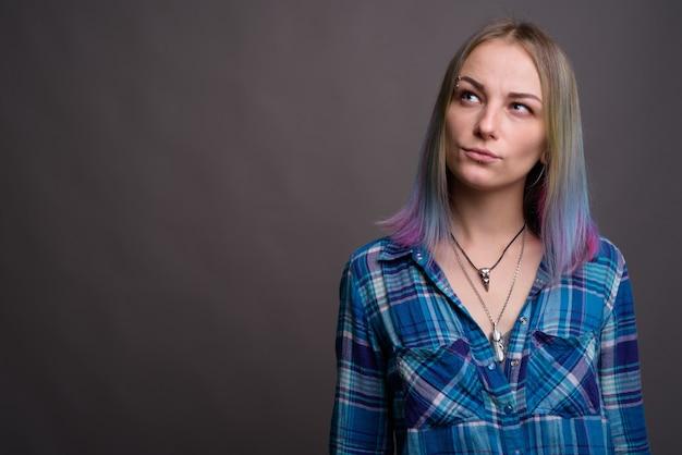Giovane bella donna ribelle con capelli multicolori