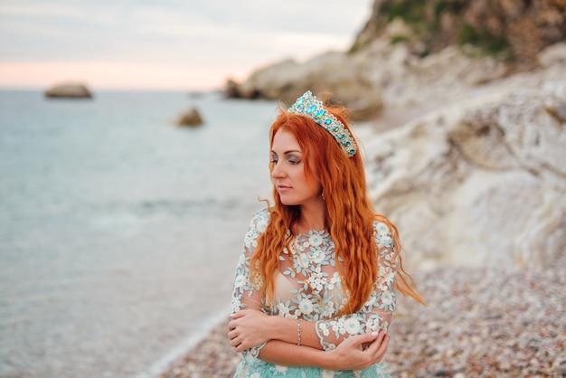 Giovane bella donna dai capelli rossi in un abito lussuoso in piedi su una costa rocciosa del mare adriatico, primo piano