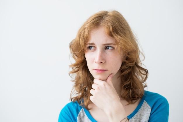 Femmina europea giovane bella rossa con espressione di dubbio e malcontento sul viso preoccupato