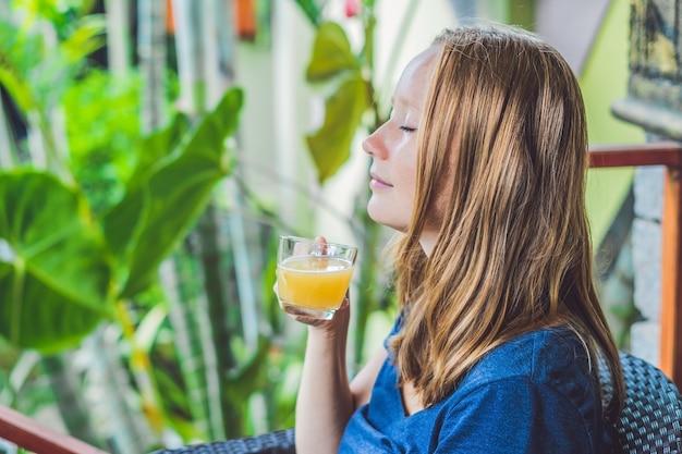 Giovane bella donna rossa che si siede in un caffè bevendo un delizioso tè allo zenzero del mattino in un caffè