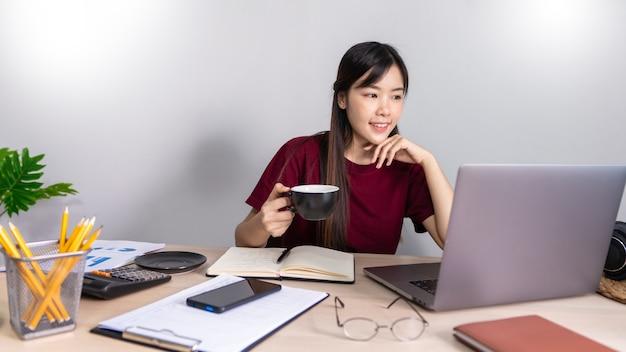 Una giovane bella ragazza asiatica di affari di relax utilizza un computer portatile che lavora a distanza da casa