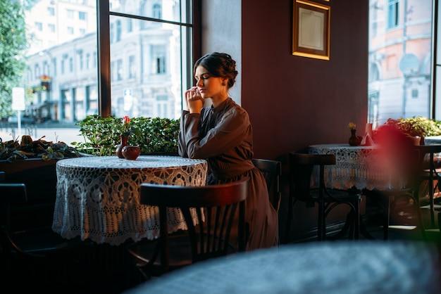 Giovane bella signora retrò nella caffetteria
