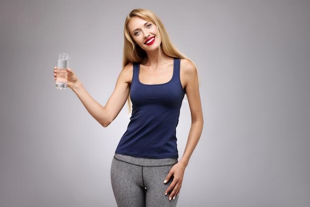 Giovane bella ragazza snella che tiene un bicchiere d'acqua.