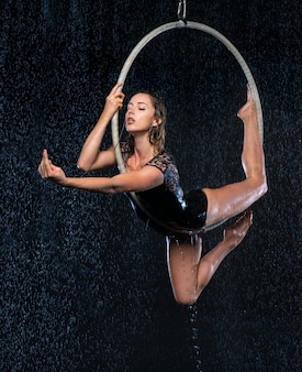 Giovane bello artista di circo sottile che fa perfomance con cerchio aereo in posa su uno sfondo di studio nero aqua.