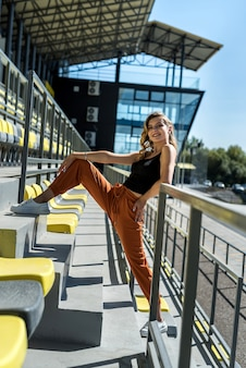 La giovane bella donna esile in abiti sportivi si rilassa vicino ai sedili nello stadio