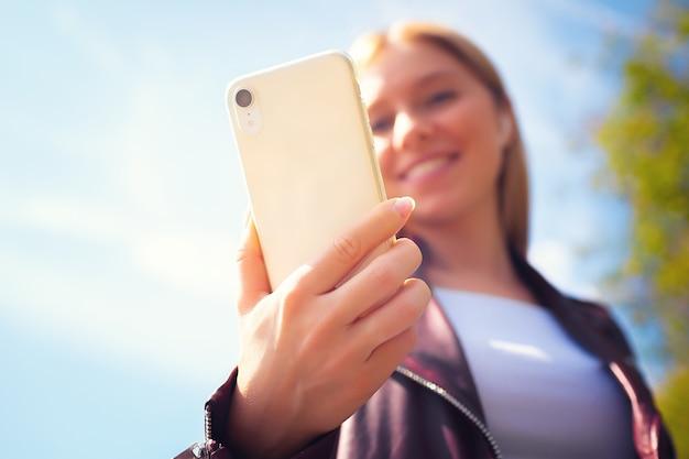Giovane bella ragazza caucasica adulta sorridente sfocatura viso camminare all'aperto nel parco con comunicazione chat con il cellulare